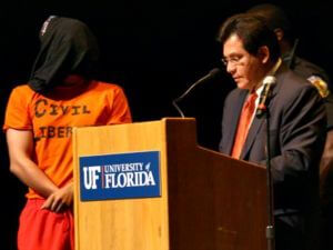 Former U.S. Attorney General Alberto Gonzales pauses during his speech as a protester stands next to him.